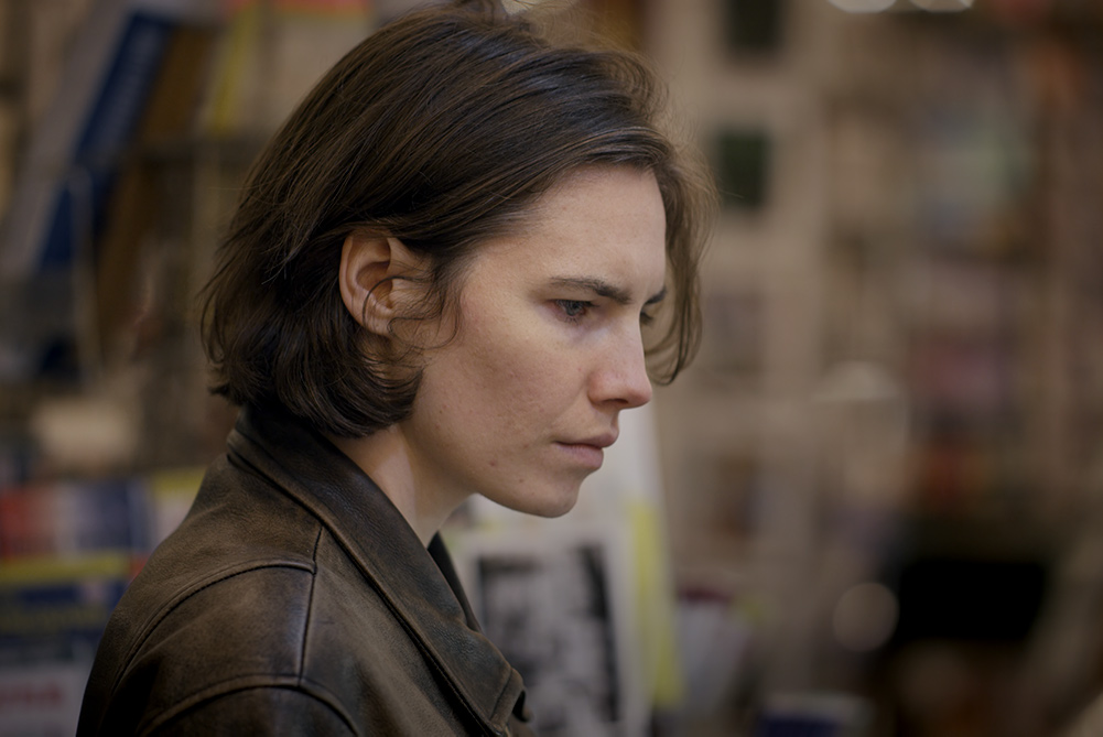 Side profile of Amanda Knox, a white woman with short brown hair. She is wearing a leather jacket. Image from Ron Blackhurst and Brian McGinn's 2016 film 'Amanda Knox.' Courtesy of Netflix.