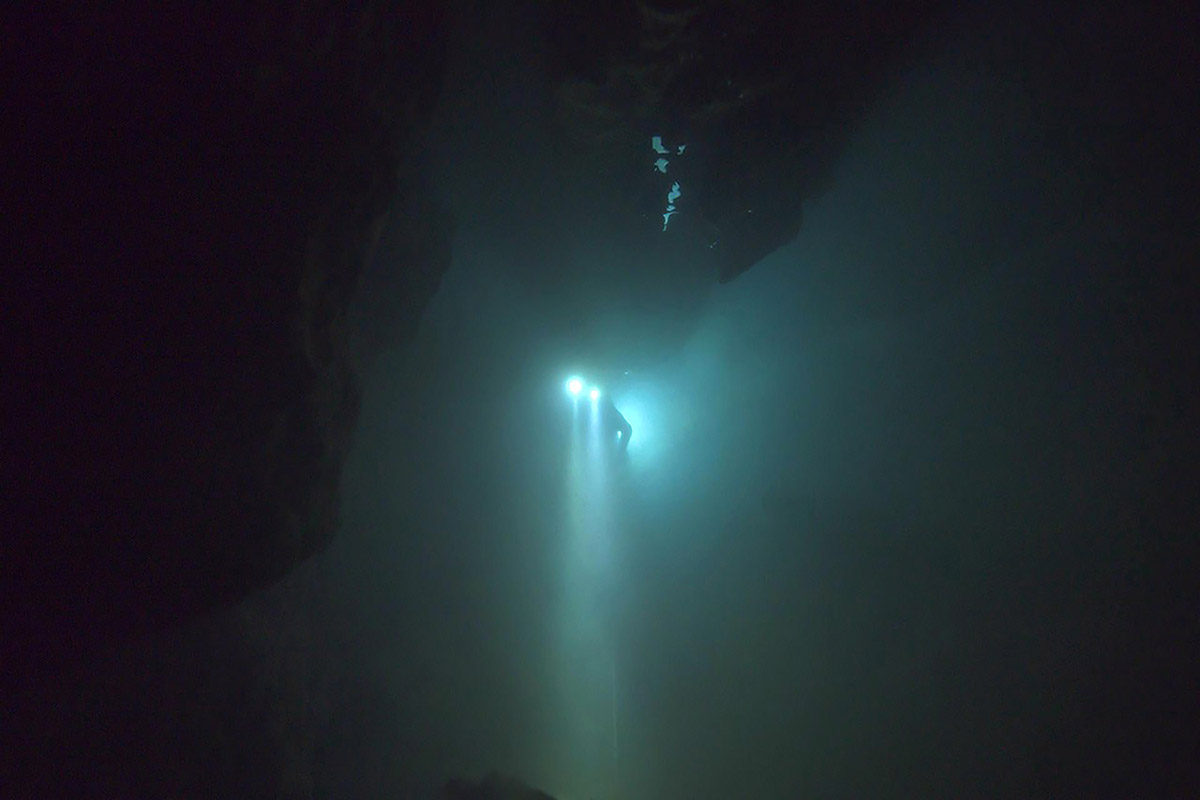 A cave diver, wearing diving equipment and two headlamps, searches in a flooded cave in Thailand for 12 boys and their soccer coach.  From  E. Chai Vasarhelyi and Jimmy Chin's 'The Rescue'  Photo: : National Geographic)