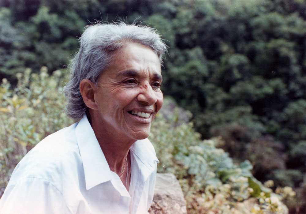Chavela Vargas is a queer Latin American singer with grey hair. She is wearing a white shirt, is smiling, and is standing amidst trees and shrubs. Image from Catherine Gund and Daresha Kyi's 'Chavela.' Courtesy of Alicia Elena Pérez Duarte, Aubin Pictures