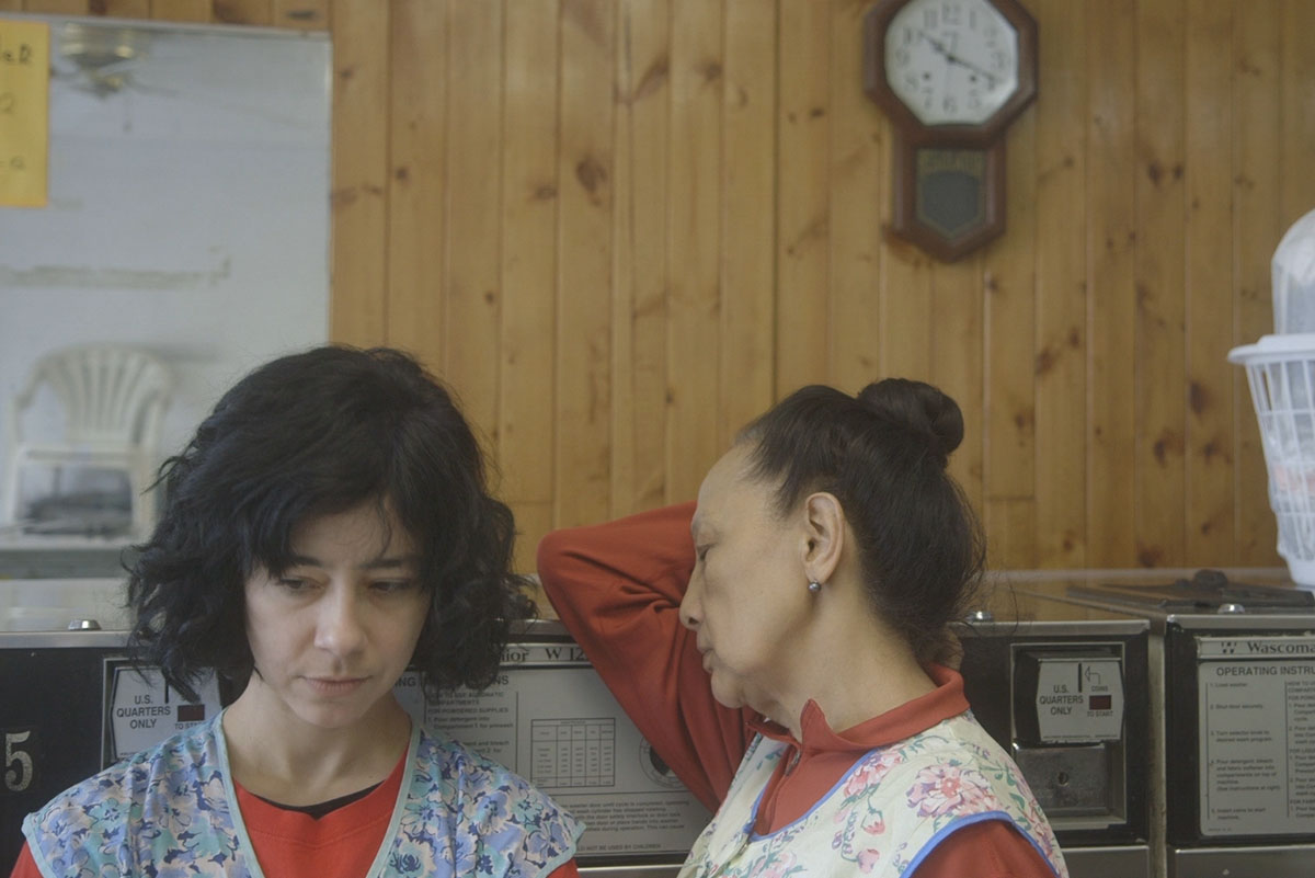 Two female laundry workers are wearing floral aprons and standing against a wooden wall. From Lynne Sachs' 'The Washing Society.' Courtesy of The Criterion Channel.