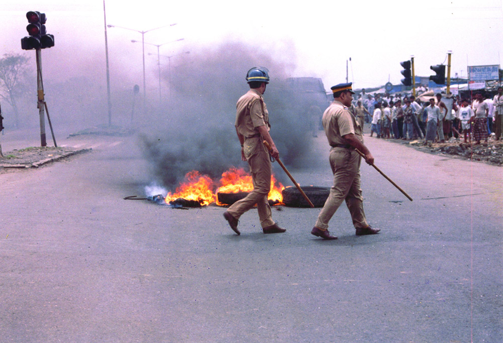 Tires burning in the middle of the road, two Indian police officers are walking by with batons in hand and crowd watching on the side of the road. Courtesy of OVID.tv