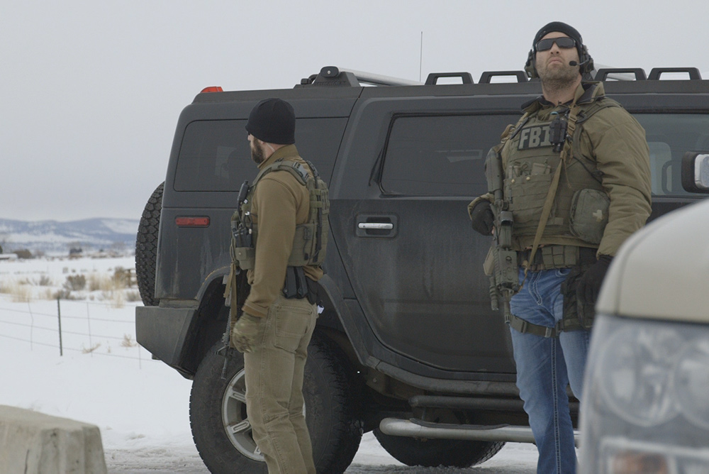 Two FBI agents in gear standing next to a big black armored SUV. From David Byars' 'No Man's Land.' Courtesy of David Byars