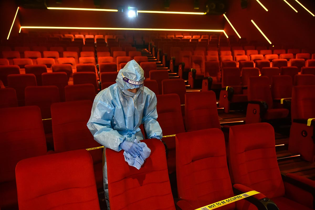 Image of a theater worker in a blue hazmat suit disinfecting red movie theater chairs