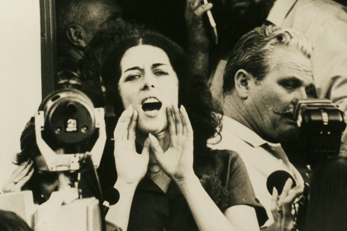 Activist Lois Gibbs is a white woman with short dark hair seen shouting to a crowd in an archival image. From Mark Kitchell's 2012 film 'A Fierce Green Fire.' Courtesy of Mark Kitchell.