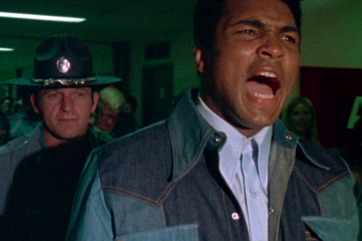 Boxer Muhammad Ali is a Black man wearing a blue shirt and a denim jacket. He is being arrested by a white policeman. From Leon Gast's 'When We Were Kings.' Courtesy of The Criterion Collection.