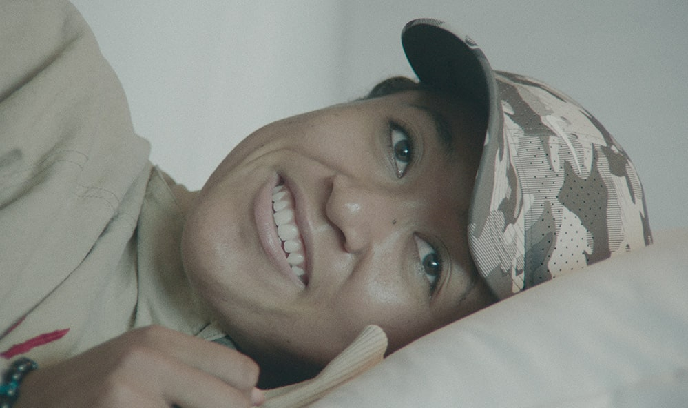Naomi Osaka, a Black and Asian bi-racial woman, lying on her side and smiling. She is wearing a camo hat. A still from Garrett Bradley's docu series 'Naomi Osaka', which was the opening night film at AFI Docs. Courtesy of Netflix.