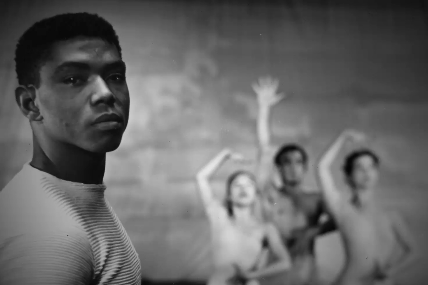 Black-and-white image of a young Alvin Ailey. He is a Black man with short hair, wearing a white t-shirt. Behind him are three dancers. Image from Jamila Wignot's 'Ailey.' Courtesy of NEON.