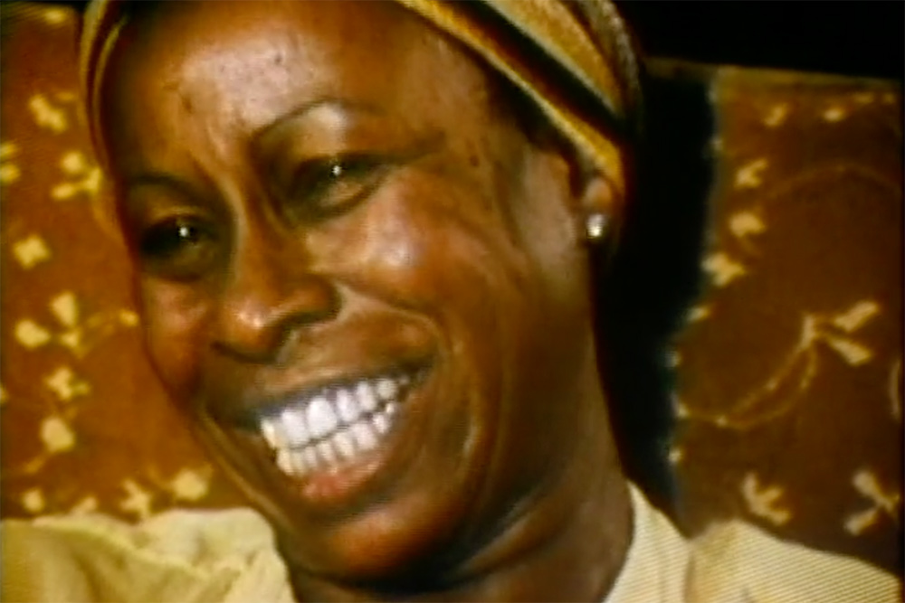 """An image of Betty Carter, a Black female jazz singer. She is smiling, wearing a golden yellow blouse and a headband. From Michelle Parkerson's """". . . But Then, She's Betty Carter"""". Courtesy of The Criterion Collection."""