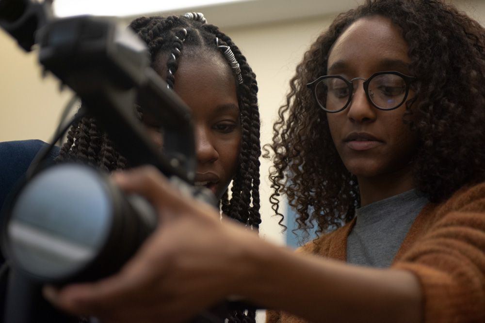 Two young Black women, students of the Newmark J School, look into a video camera screen. Photo by Marco Poggio.