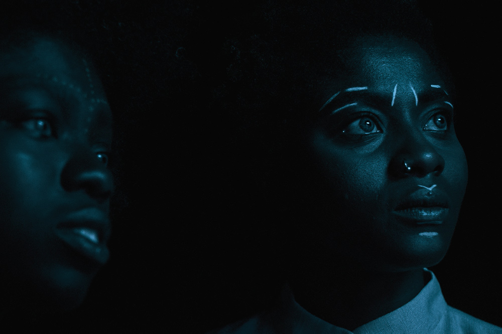 Two young Afro-German women photographed in low light. They have white traditional markings drawn on their faces. Image from Anna Zhukovets' and Kokutekeleza Musebeni's 'Door of Return.' Courtesy of BlackStar Film Festival.
