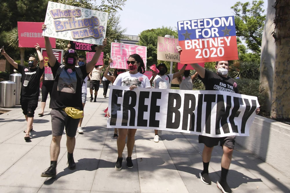 A group of people on the street holding up signs that read 'Free Britney.' It's daytime and they are wearing masks. Image from 'Framing Britney Spears.' Courtesy of New York Times Op Docs.