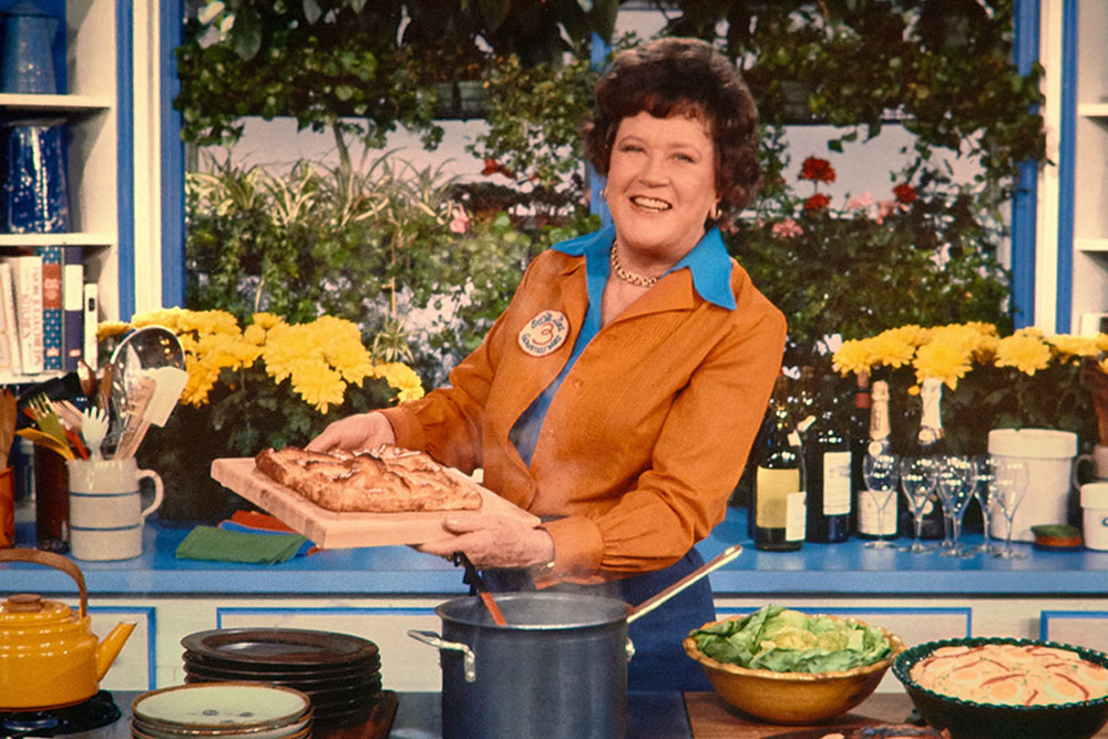 Julia Child is a white female chef with short brown wavy hair. Here she is standing in her kitchen holding a tray of pastry. She is wearing a blue shirt underneath another brown one, and is smiling. Image from Julie Cohen and Betsy West's 'Julia.' Courtesy of TIFF.