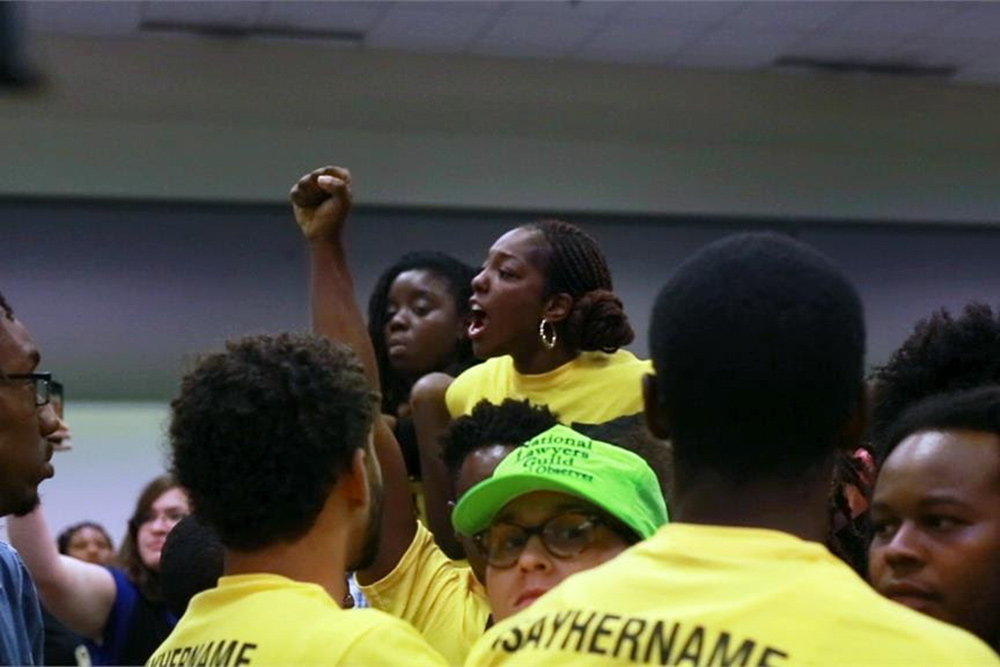"""Caption: Janaé Bonsu is a young Black woman leading an activist gathering. She and her comrades are in yellow shirts that say """"Say Her Name"""". Image from Ashley O'Shay's 'Unapologetic'. Courtesy of David Magdael & Associates."""