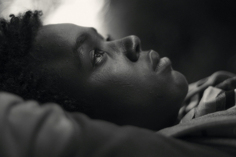 Mohammed Arif, a boy from Ethiopia, lies on his back with eyes looking up at the sky. Image from Jessica Beshir's 'Faya Dayi.' Courtesy of Cinetic Media.