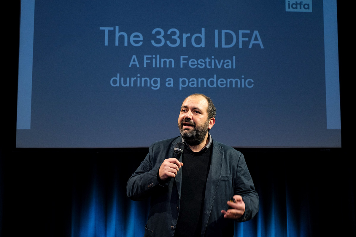 IDFA Artistic Director Orwa Nyrabia is a Syrian man with a beard and short hair. He is wearing a black jacket and a sweater and is addressing the in-person and virtual audience at IDFA 2020. There is a screen behind him. Photo: Coen Dijkstra. Courtesy of IDFA