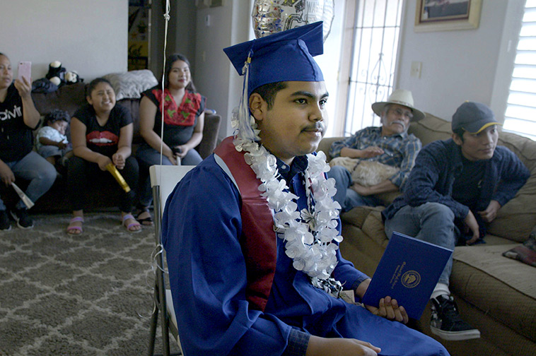 Denilson Garibo is a young man in a blue graduation gown. He is wearing a graduation hat and has a garland of white plastic flowers around his neck. He is surrounded by family members. From Peter Nicks' 'Homeroom.'' Courtesy of Hulu