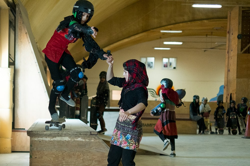 A young Afghani girl in a checkered headscarf helps her friend on a skateboarding ramp. Her friend is in skateboarding gear. They're inside a training room with other young skateboarders. Image from Carol Dysinger's 'Learning to Skateboard in a Warzone (If You're a Girl).' Courtesy of the filmmaking team.