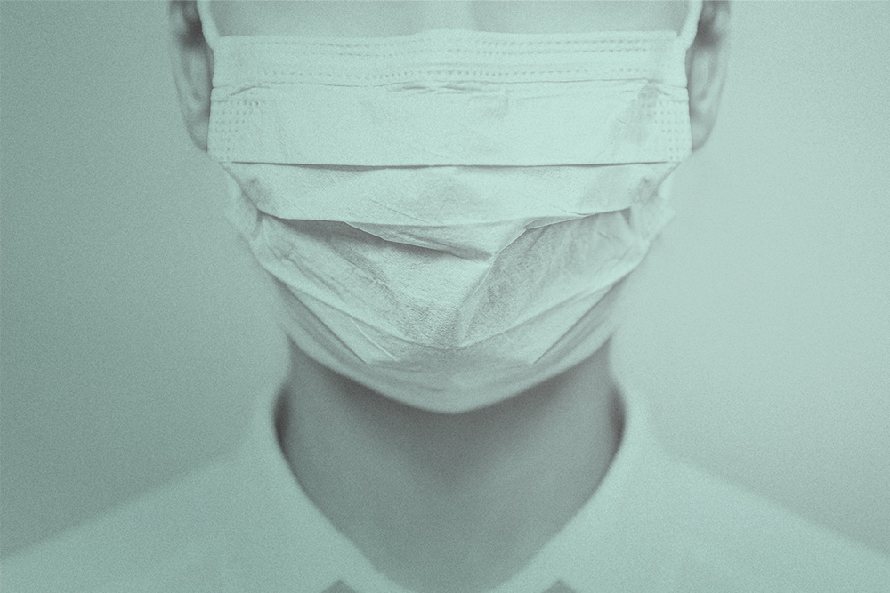 A close up shot of a woman with white skin wearing a white face mask.