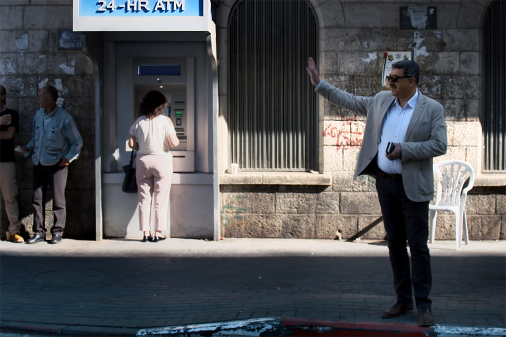 Musa Hadid, the mayor of Ramallah, is a middle-aged man with a moustache. He is waving to someone and is wearing sunglasses, as well as a grey jacket with a shirt and trousers. There are passersby and an ATM machine behind him. Image from David Osit's 'Mayor.' Courtesy of David Osit and POV.