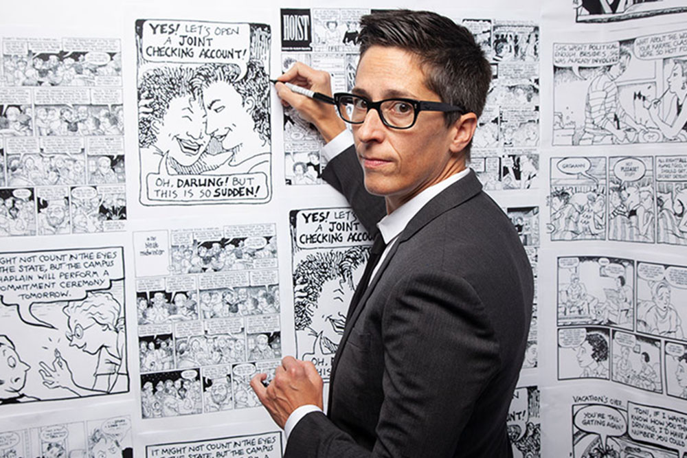 Alison Bechdel is a white woman with short hair black-rimmed glasses. She is wearing a black suit and is holding a marker to a wall of her comics. Image from Vivian Kleinman's 'No Straight Lines: The Rise of Queer Comics.' Courtesy of Outfest.