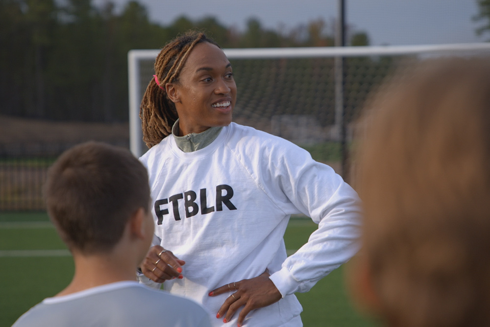 """Soccer player Jessica McDonald is a Black woman in her 30s. Here, she is smiling, wearing a white shirt that says """"FTBLR"""" and her hair is tied back. Image from Andrea Nix Fine and Sean Fine's 'LFG.' Courtesy of HBO Max"""