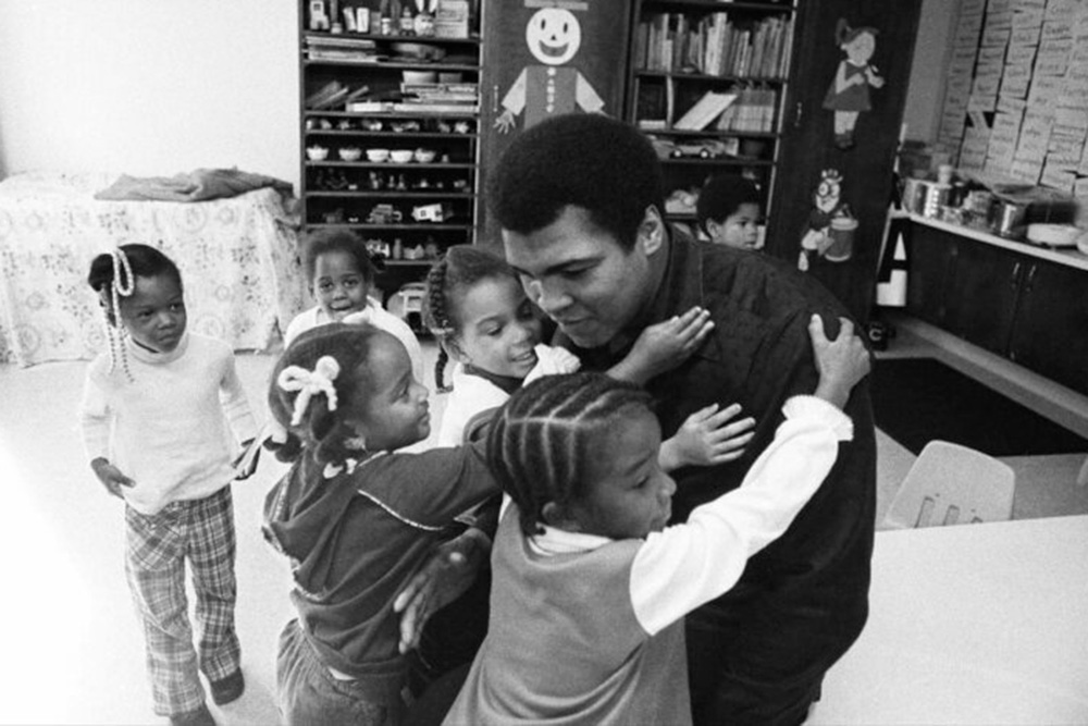 Muhammad Ali, a Black boxer, on a visit to his old grammar school in Louisville, KY, in 1977. He is surrounded by young Black children who are hugging him. From 'Muhammad Ali,' a four-part documentary from Ken Burns, Sarah Burns and David McMahon. Photo by Michael Gaffney. Courtesy of PBS.