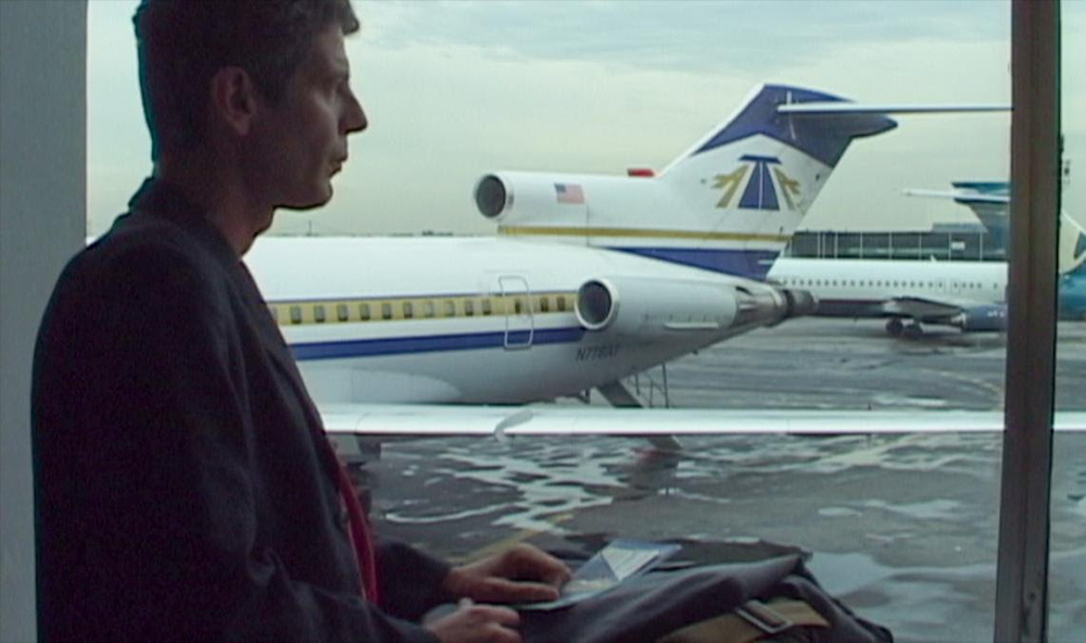 Profile of Anthony Bourdain, a white man in a jacket, against blue and white stationary airplanes. Still from Morgan Neville's 'Roadrunner: A Film About Anthony Bourdain.' Courtesy of Cinetic Media.