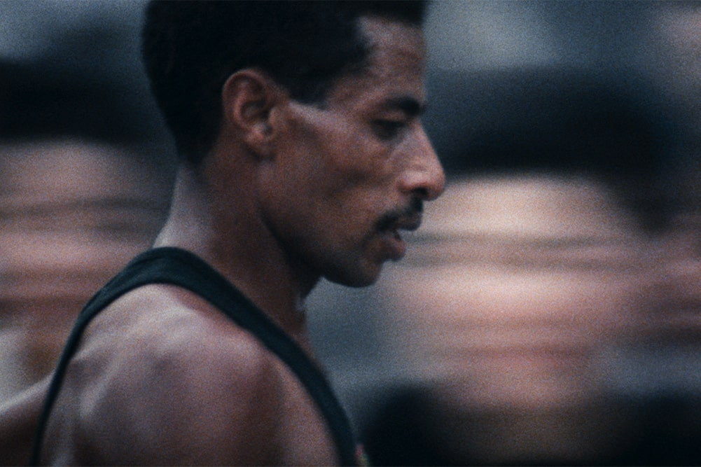 Abebe Bikila is a Black Ethiopian marathoner seen here at the 1964 Summer Olympics in Tokyo. He has black hair, a moustache, and is wearing a black vest. Image from Kon Ichikawa's 'Tokyo Olympiad.' Courtesy of The Criterion Collection.