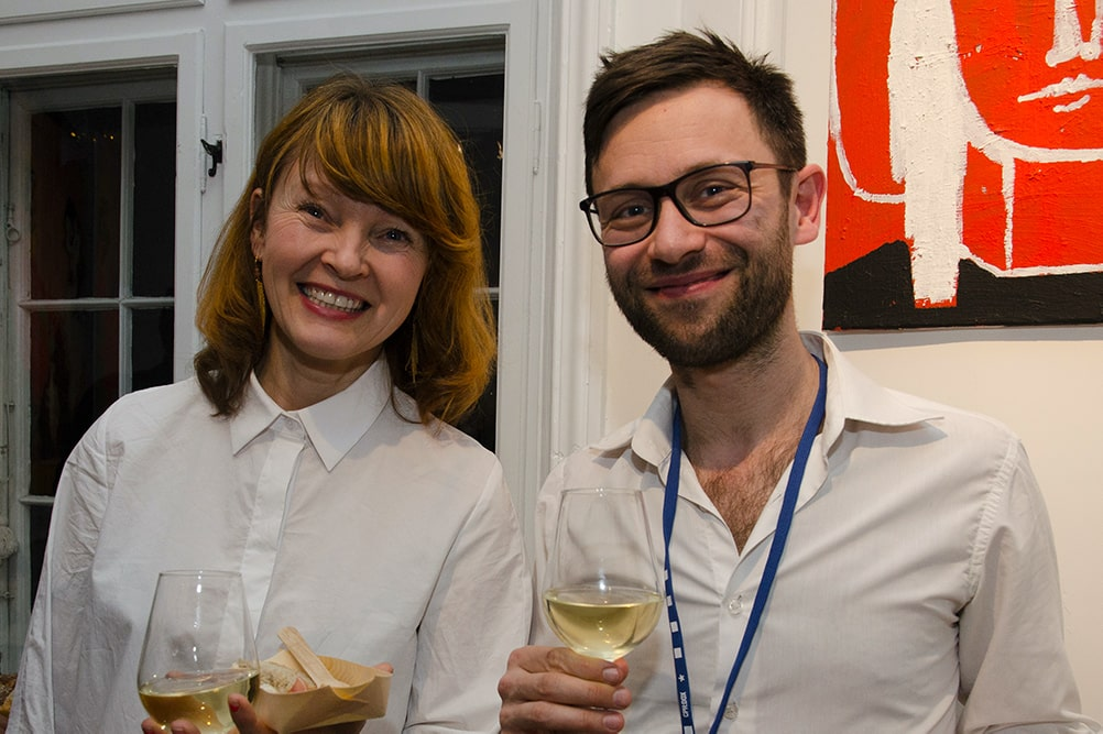 Tine Fischer, a white woman with shoulder-length dirty-blond hair in a white shirt with Niklas Engstrøm, a white man with brown hair, beard, and black frame glasses. He is also wearing a white shirt. Courtesy of CPH:DOX.