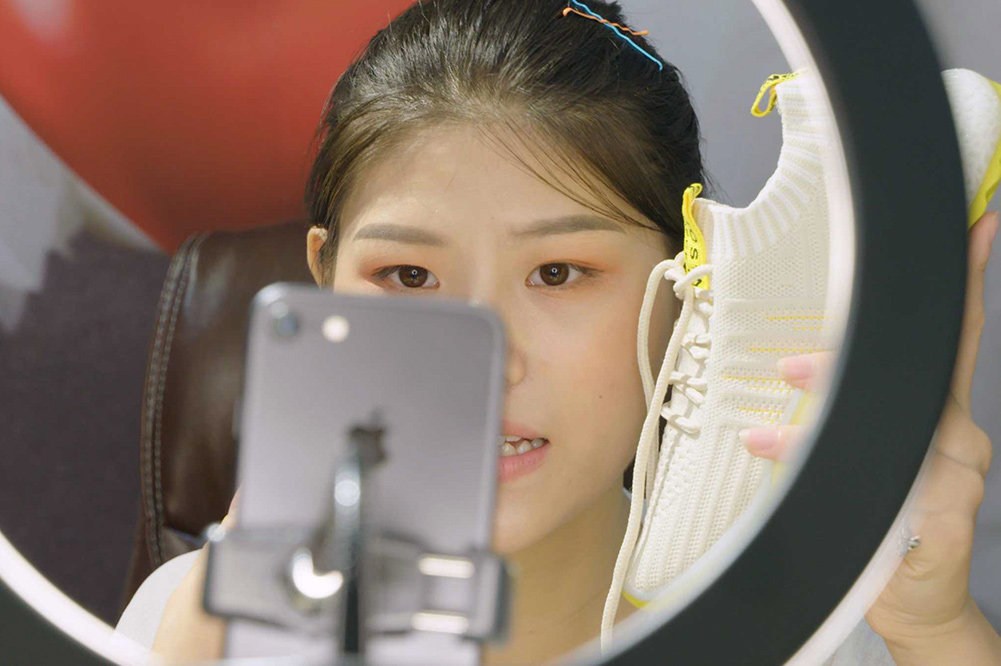 A young Chinese woman recording herself on an iPhone, holding a sneaker. There is a ring light in front of her. Image from Jessica Kingdon's 'Ascension.' Courtesy of Tribeca Festival