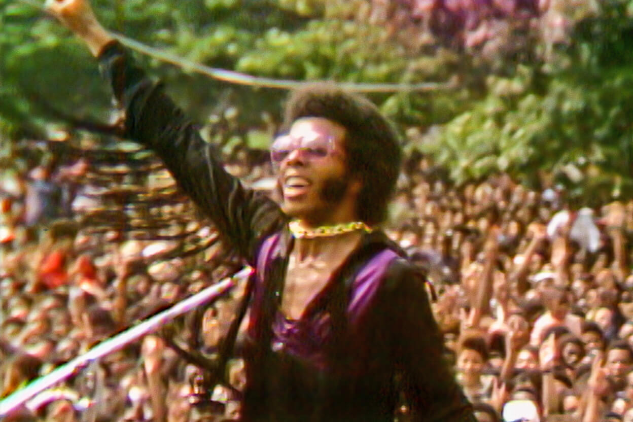 Sly Stone, a Black male musician, in violet and black, plays to a huge crowd in Questlove's 'Summer of Soul' (Director: Questlove; Producer: David Dinerstein, Robert Fyvolent, Joseph Patel) Courtesy of Cinetic Media.