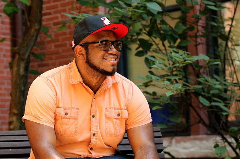 Headshot of a smiling Black adult man sitting on a bench in a black and red hat, glasses, and an orange button-up shirt.