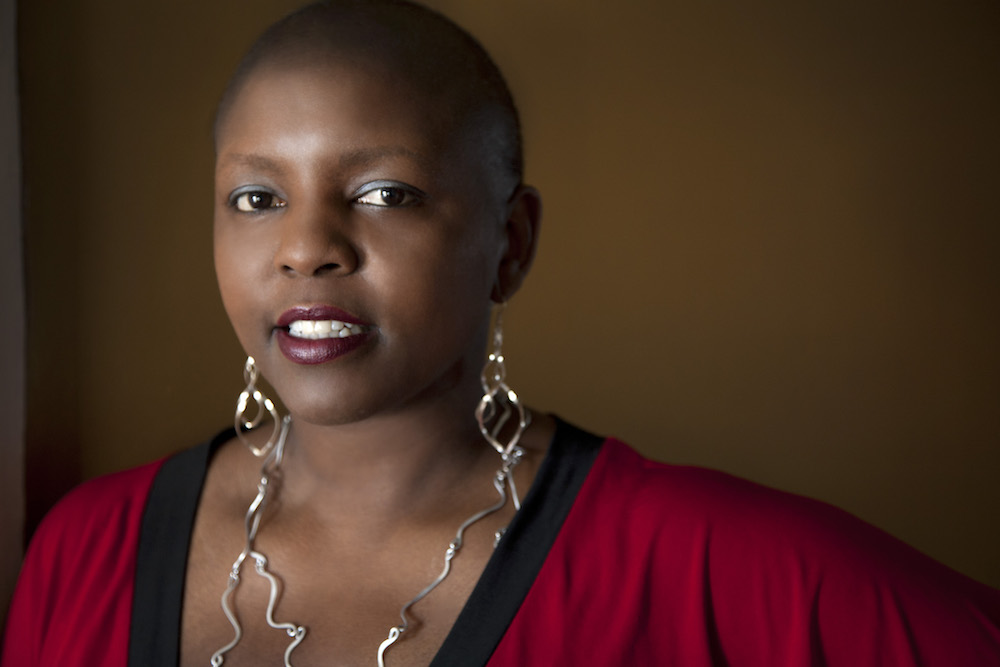 Yoruba Richen is an African American woman. She has a shaved head and is sporting large abstract dangled metal earrings that reaches her chest. She is wearing a red V-neck top with contrasting black neck band.