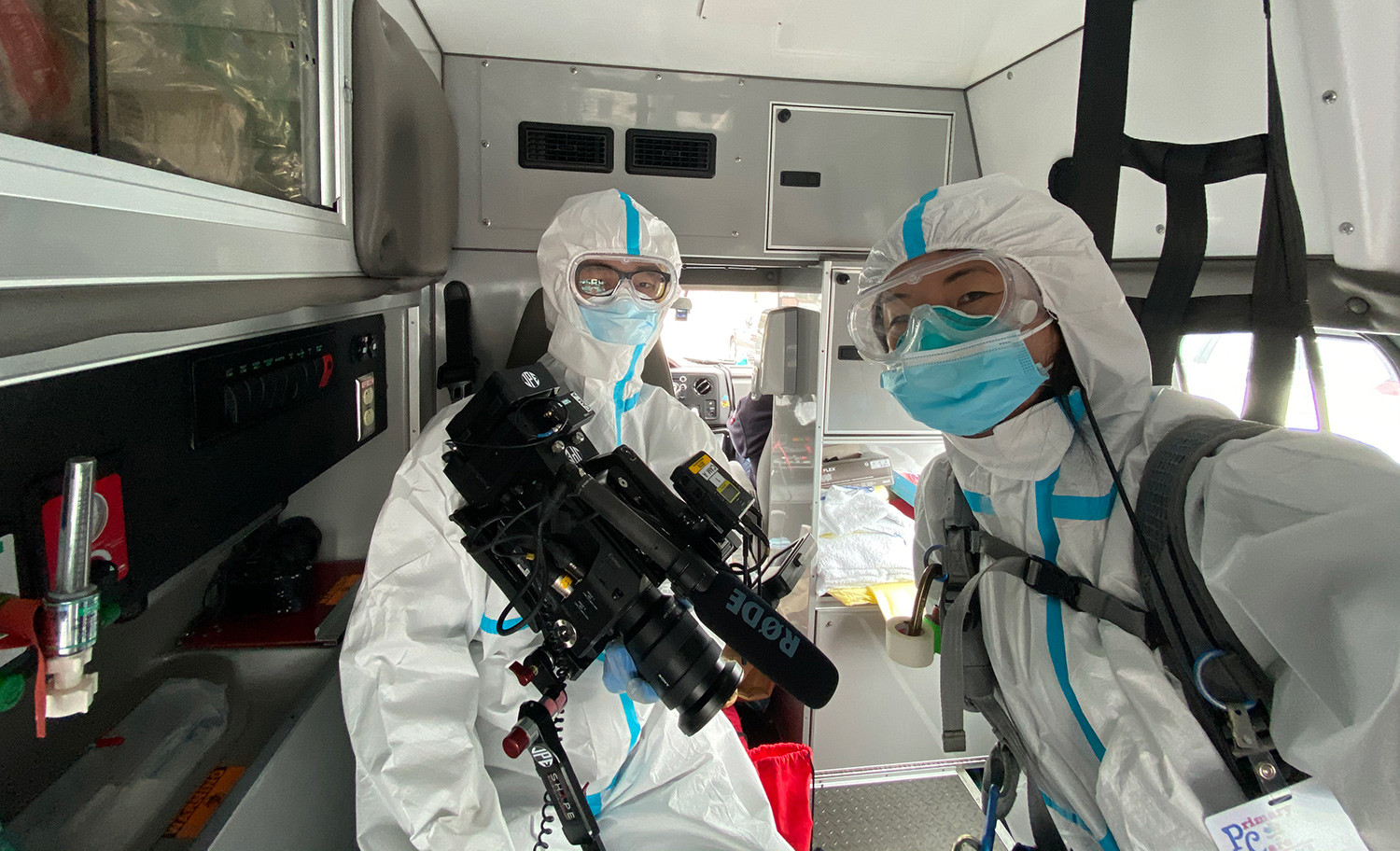 Location sound mixer Emily Strong in production in New York City at the height of the COVID-19 pandemic. They are in white protective coverall suit with disposable mask and goggles inside a van. Courtesy of Emily Strong