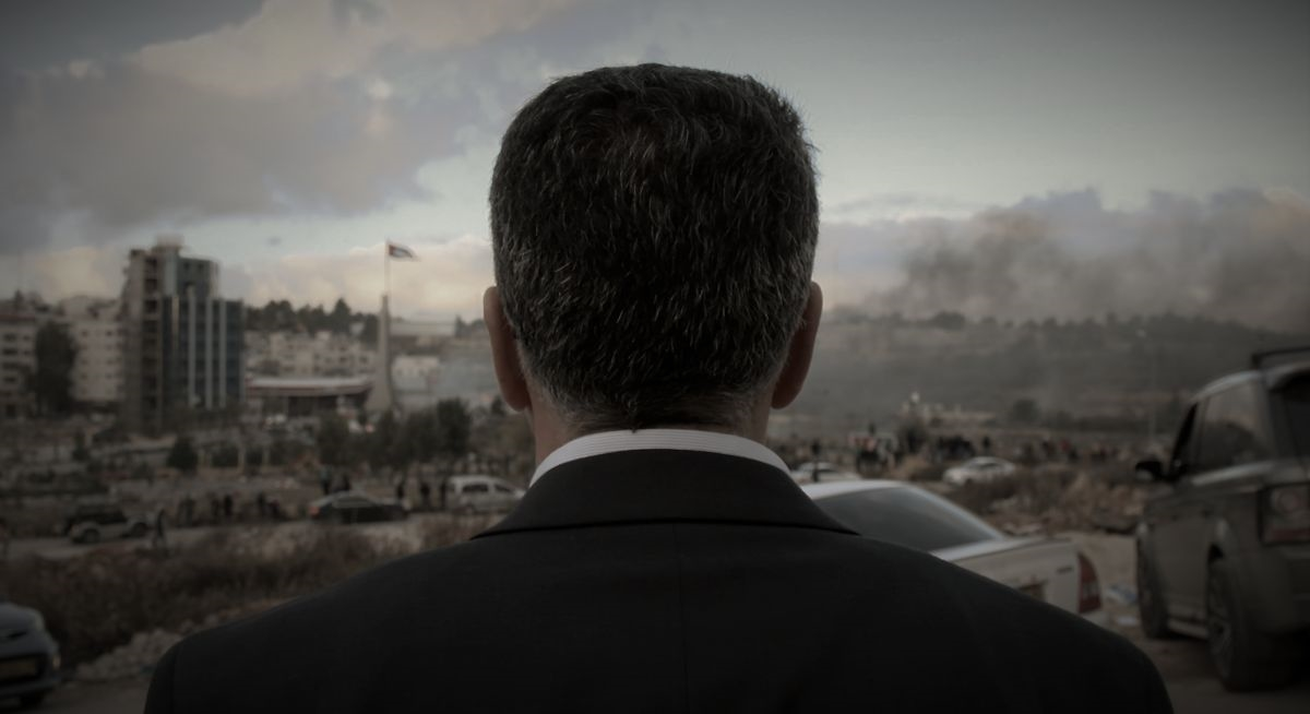 Back of a man in suits facing Ramallah, de facto capital of Palestine