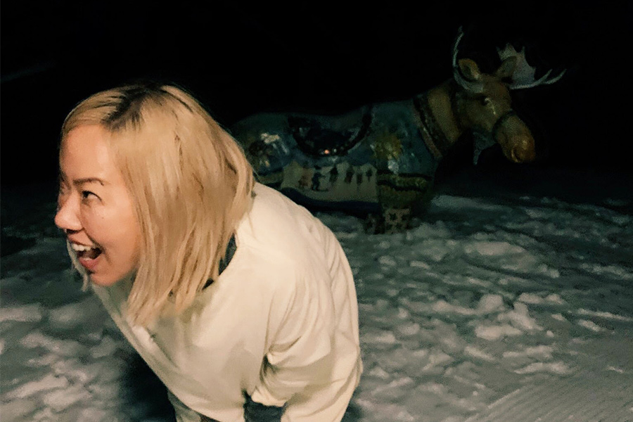 Sue Kim is a woman of Korean-descent, she has a big smile and blonde hair to her shoulders. She is looking to her right, out in the snow at night with a moose sculpture behind her.