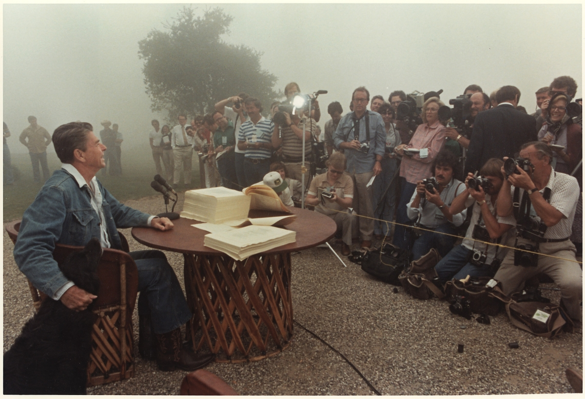 President Ronald Reagan signs the Economic Recovery Tax Act of 1981, Rancho del Cielo, CA, 1981. As seen in 'The Reagan Show,' directed by Pacho Velez and Sierra Pettengill. Photo:: Karl Schumacher. Courtesy of Ronald Reagan Presidential Library. (Gravitas Ventures & CNN Films)