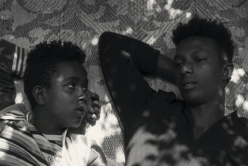 Black and white photo of two young Black men lying on a mat. (l. to r.) Mohammed Arif and Ibrahim Mohammed, two boys from Harar, Ethiopia, as seen in 'Faya Dayi', directed by Jessica Beshir. Courtesy of Merkhana Films.