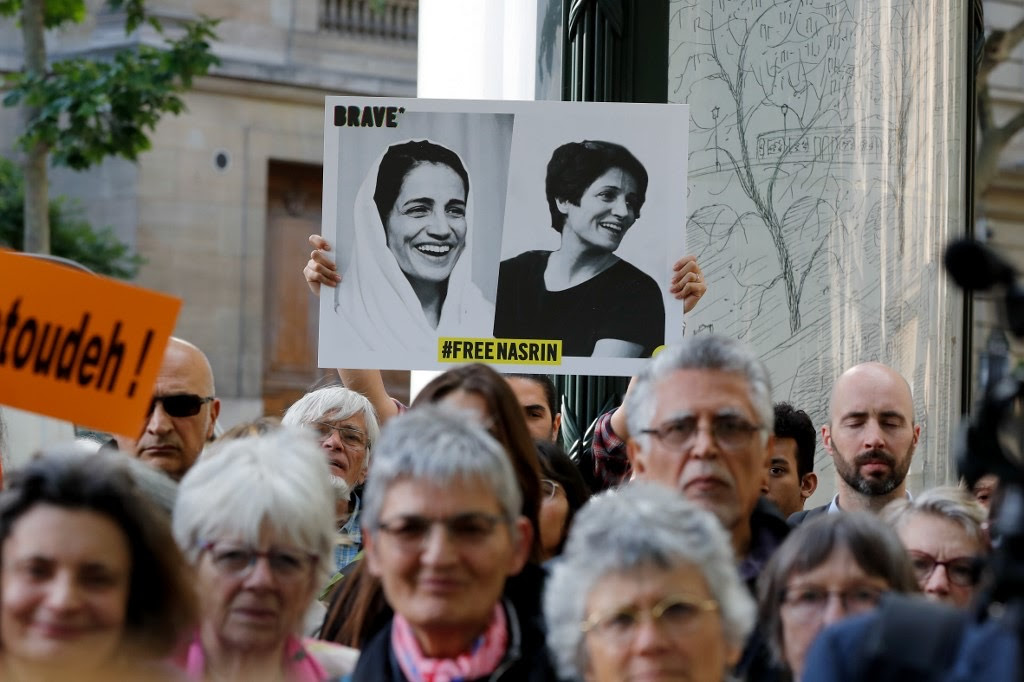 """A protestor holds up a banner with Nasrin Sotoudeh's photo. It says """"Free Nasrin."""" From 'Nasrin' (Director: Jeff Kaufman). Courtesy of David Magdael & Associates"""
