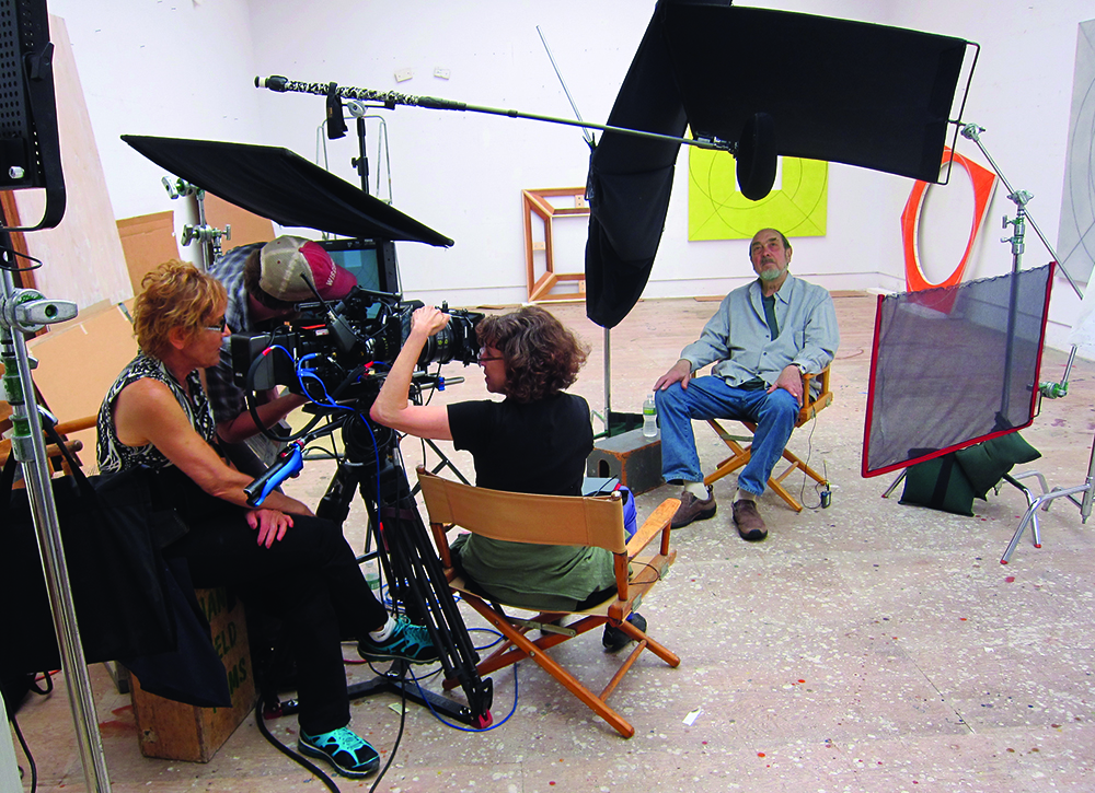 Shooting Robert Mangold at his studio in Upstate New York, 2013. Director of Photography Nancy Schreiber and Director Marcie Begleiter in foreground Production Photo.
