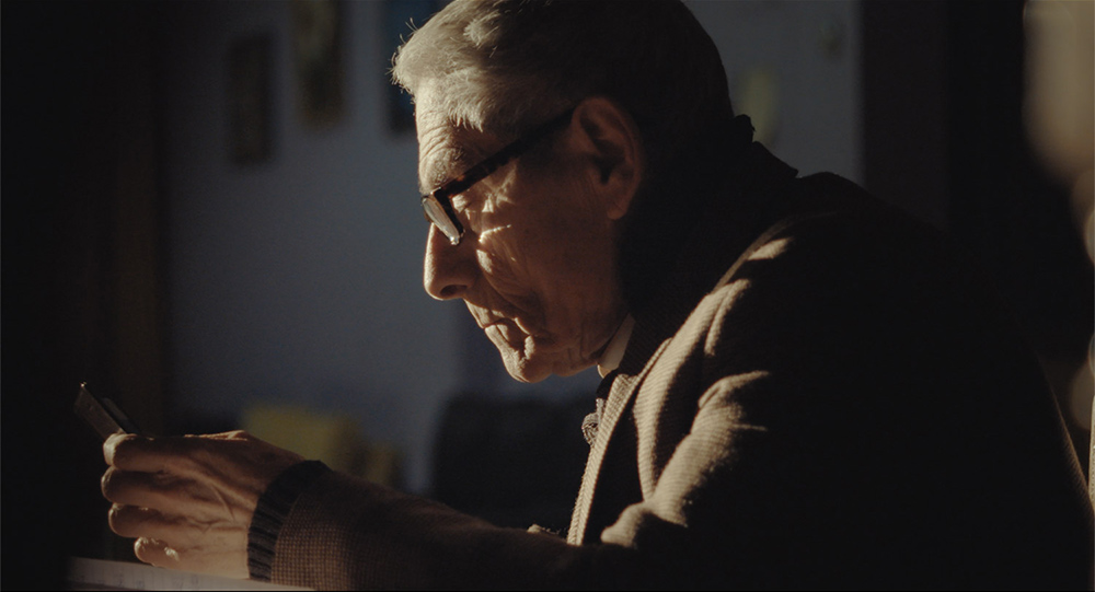 The noir lighting of Sergio dictating a late-night memo; from Maite Alberdi's 'The Mole Agent'. Courtesy of Gravitas Ventures