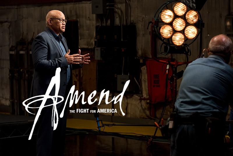 Larry Wilmore, an African American male film director, is wearing a black blazer over a blue shirt, talking to someone off screen on a film set.