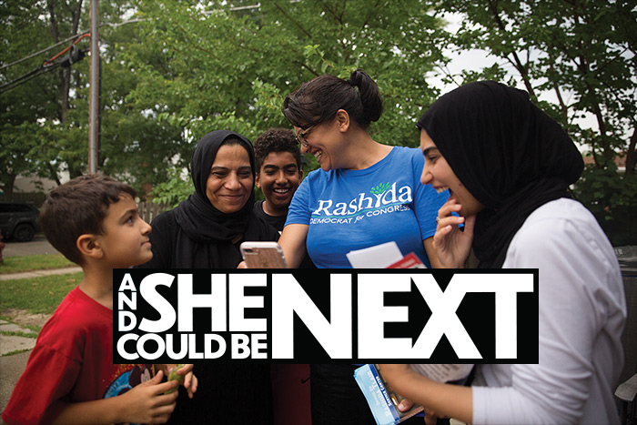 Congresswoman Rashida Tlaib in a blue tshirt on her campaign, surrounded by a family of Muslim supporters