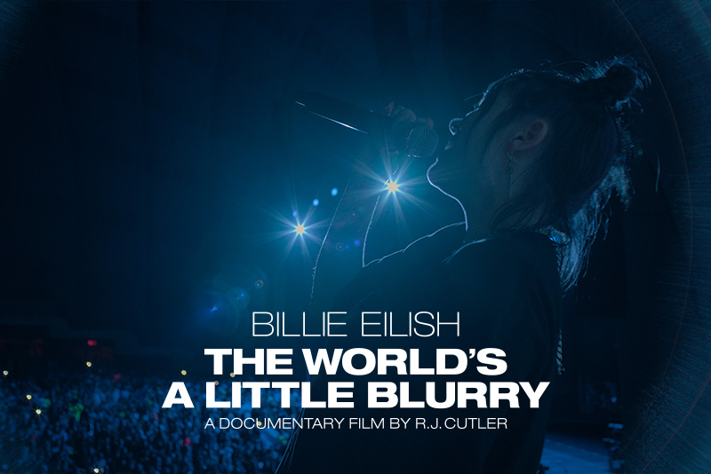 Billie Eilish singing to a crowd with blue lights shining in the background