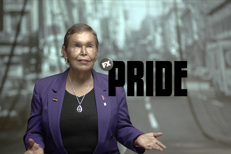 Elder adult with medium skin tone, short ash blonde hair, wearing a purple blazer over a black tee.