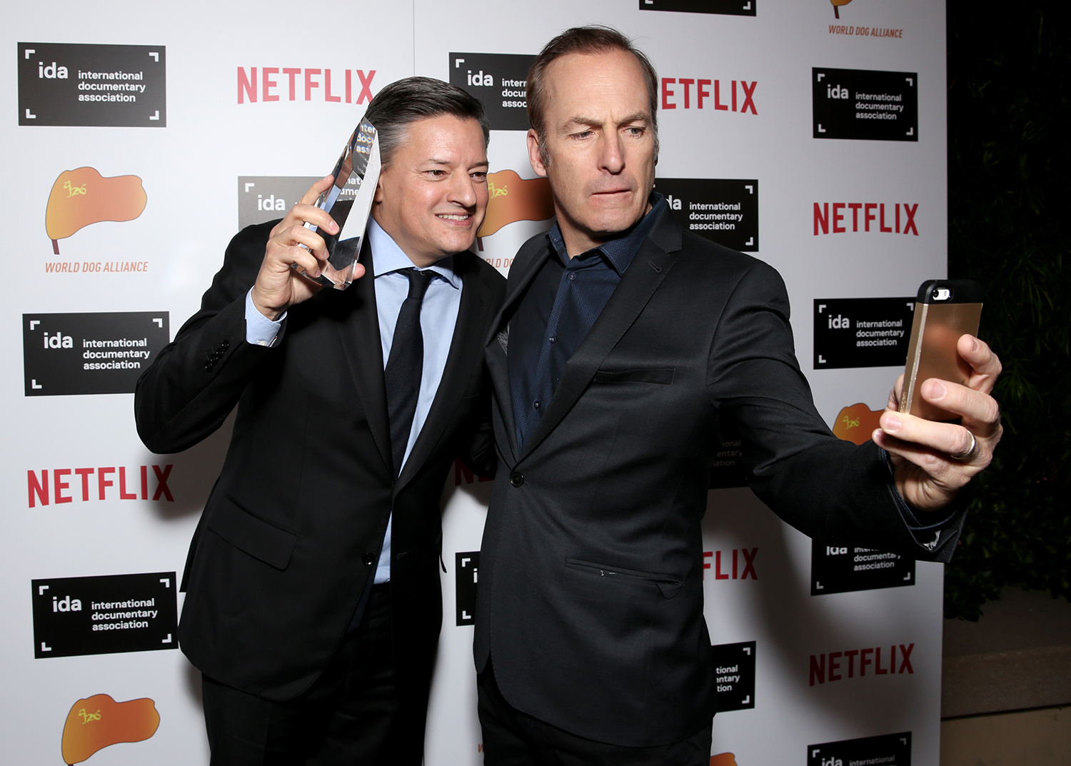 Netflix's Ted Sarandos poses with the Pioneer Award backstage with actor Bob Odenkirk