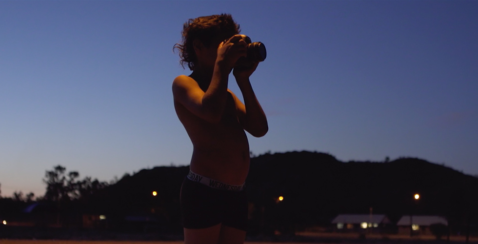 Image from 'In My Blood It Runs' by Maya Newell. At dusk, 10-year-old Dujuan Hoosan is taking a picture with a camera.