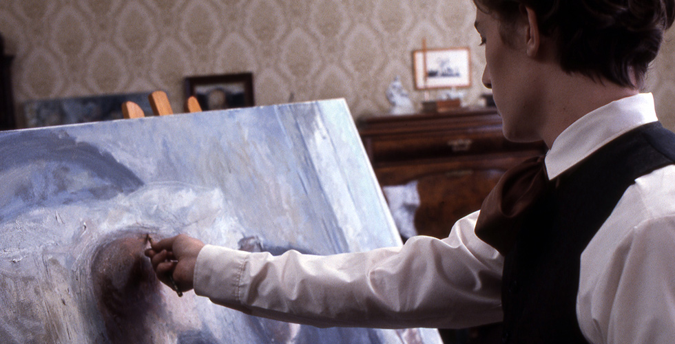 Film still from Peter Watkins' Edvard Munch where an actor is playing a young Munch, adding details to a painting.