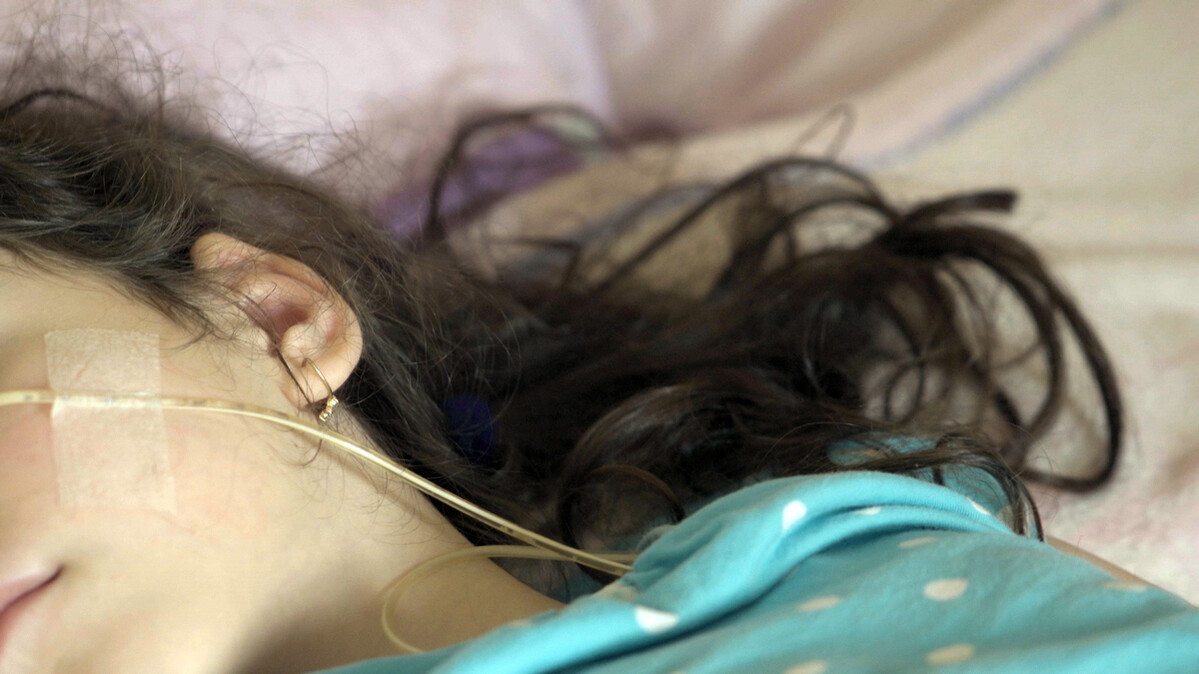 A girl with dark brown hair is lying on the bed, being nourished via feeding tube