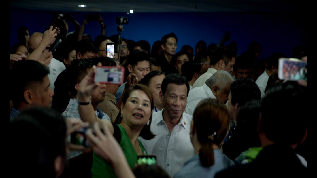 President of the Philippines Rodrigo Duterte is surrounded by a crowd, many holding up phones to take photos